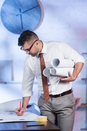 architect writing on blueprint while holding rolled plans in office