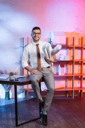 Photo pour Heureux architecte assis sur le bureau, tenant roulé des plans et regardant la caméra - image libre de droit