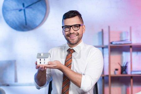 fröhlicher Architekt in Brille mit Hausmodell und lächelnd in die Kamera