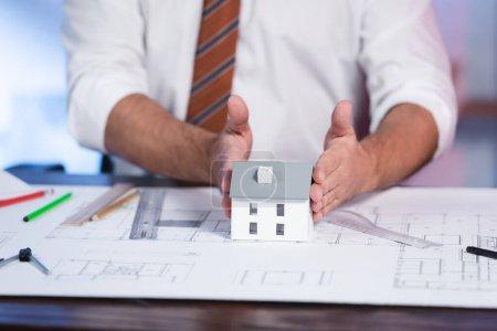 Photo pour Vue recadrée du modèle de maison de touche architecte près du plan directeur sur le bureau, fond flou - image libre de droit