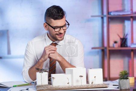 Photo pour Architecte souriant assis sur le lieu de travail près de maisons modèles - image libre de droit