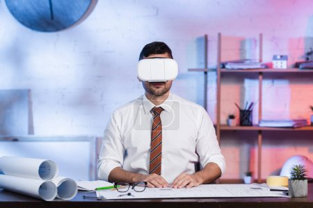 Photo pour Architecte en vr casque assis sur le lieu de travail près des plans - image libre de droit