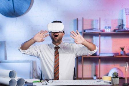 Photo pour Architecte étonnant geste dans le casque vr près des plans sur le bureau - image libre de droit