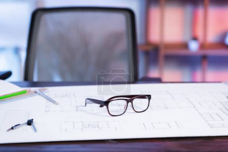 Photo pour Mise au point sélective des lunettes et du plan sur le bureau de l'agence d'architecture, fond flou - image libre de droit
