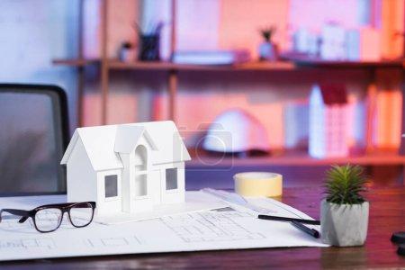 Photo pour Modèle de maison près du plan et des lunettes sur le bureau de l'agence d'architecture - image libre de droit