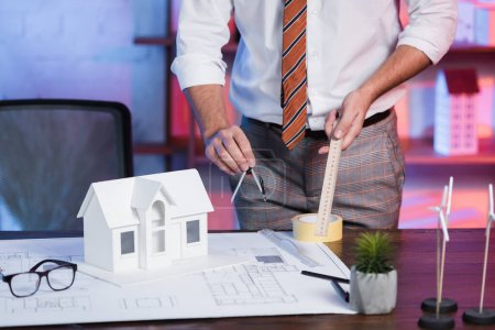 Photo for Partial view of architect with ruler and divider near house model and blueprint at workplace - Royalty Free Image