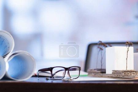 Photo pour Foyer sélectif des lunettes près des plans roulés sur le bureau - image libre de droit