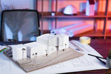 Photo pour Constructions modèles près de plan sur bureau dans bureau d'architecture - image libre de droit