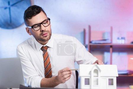 architecte sérieux dans les lunettes pointant avec crayon à la maquette maison