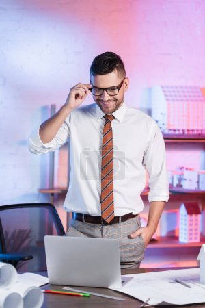 Photo pour Architecte souriant ajuster les lunettes tout en se tenant la main dans la poche sur le lieu de travail - image libre de droit