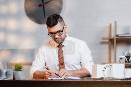 fokussierter Architekt arbeitet in der Nähe von Häusern Modelle in Architekturbüros