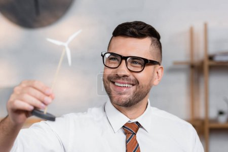 cheerful architect in eyeglasses smiling while holding model of wind turbine