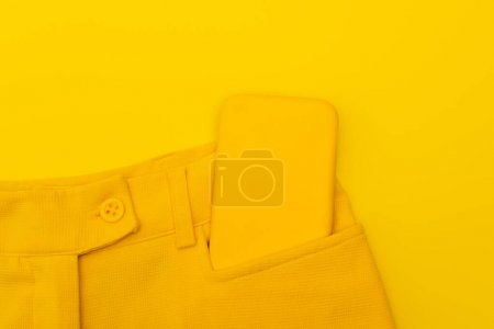 top view of smartphone in pocket of pants isolated on yellow