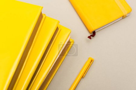 top view of yellow notebooks near pen isolated on grey