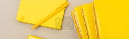 Photo for Top view of yellow notebooks near pen isolated on grey, banner - Royalty Free Image