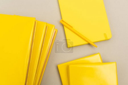 Photo for Top view of yellow notepads near pen isolated on grey - Royalty Free Image