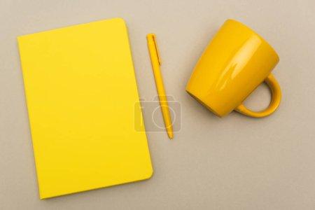Photo pour Vue du haut du carnet jaune près du stylo et tasse vide isolé sur gris - image libre de droit