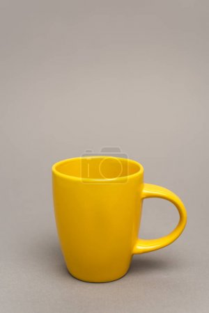 yellow mug with hot beverage on grey with copy space