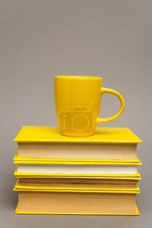 Photo pour Tasse sur pile de carnets jaunes isolés sur gris - image libre de droit
