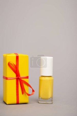 wrapped yellow gift box near bottle with nail polish isolated on grey