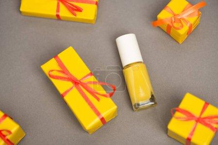 Photo pour Vue grand angle des boîtes-cadeaux jaunes enveloppées près de la bouteille avec vernis à ongles sur gris - image libre de droit