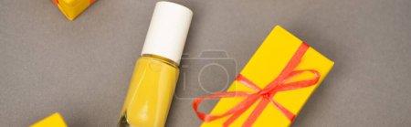 hochwinkelige Ansicht der verpackten gelben Geschenkschachtel in Flaschennähe mit Nagellack auf grau, Banner
