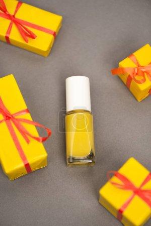 vista de ángulo alto de cajas de regalo envueltas cerca de la botella con esmalte de uñas amarillo en gris