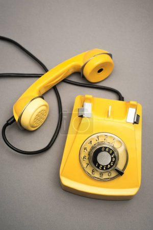 vue de dessus du téléphone rétro et jaune sur fond gris