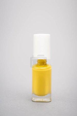 Flasche mit gelbem Nagellack auf grauem Hintergrund