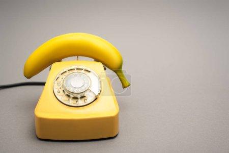 Photo for Yellow banana on retro telephone on grey background - Royalty Free Image