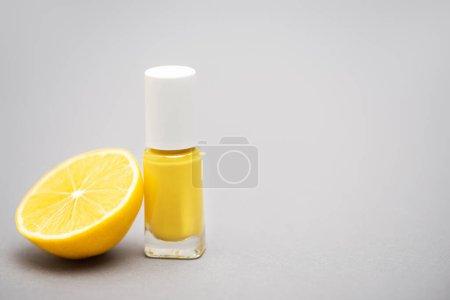 Flasche mit gelbem Nagellack und einer halben Zitrone auf grauem Hintergrund