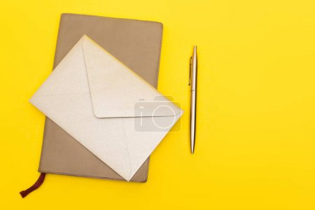 top view of envelope on notebook near pen isolated on yellow