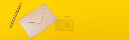 Photo for Top view of envelope near golden pen isolated on yellow, banner - Royalty Free Image