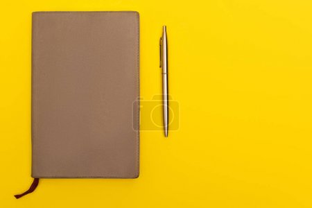 top view of copy book near golden pen isolated on yellow