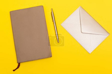 Photo for Top view of envelope near copy book and golden pen isolated on yellow - Royalty Free Image