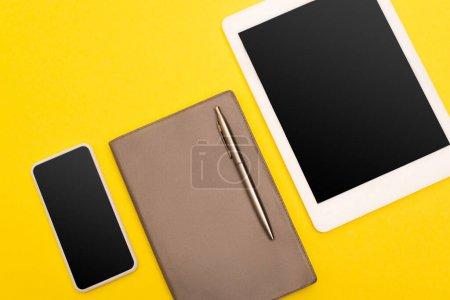 top view of gadgets with blank screen near copy book with golden pen isolated on yellow