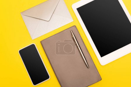 Photo for Top view of devices with blank screen near copy book with golden pen near envelope  isolated on yellow - Royalty Free Image