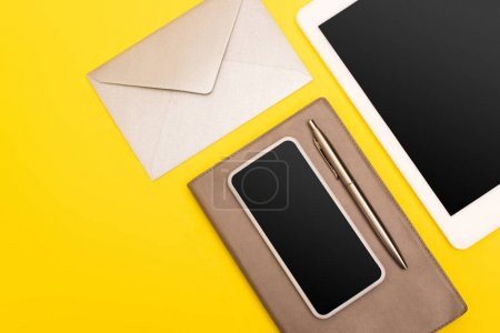 top view of devices with blank screen near notebook with golden pen near envelope  isolated on yellow