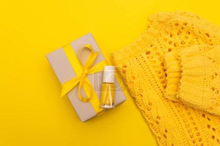 Photo pour Vue du dessus du vernis à ongles sur présent enveloppé près du cavalier isolé sur jaune - image libre de droit