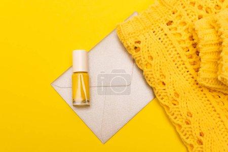 Draufsicht auf Flasche mit Nagellack, in der Nähe von Kleidung und Umschlag isoliert auf gelb