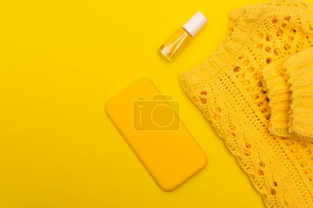 Photo pour Vue du dessus de la bouteille avec vernis à ongles, smartphone au cas où près du cavalier isolé sur jaune - image libre de droit