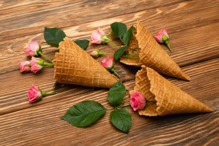 Photo for Pink flowers with leaves in waffle cones on wooden surface - Royalty Free Image