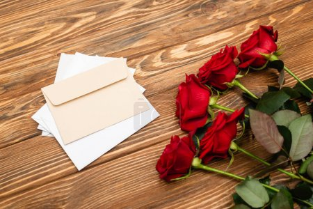 Photo pour Vue grand angle des roses rouges près des enveloppes et des papiers sur la surface en bois - image libre de droit