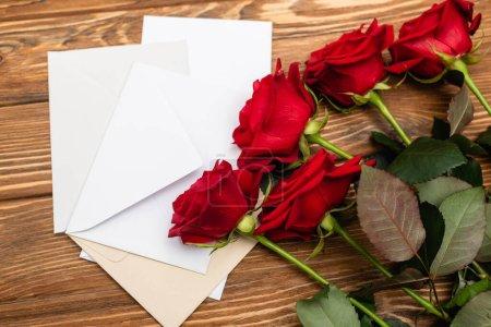 Photo pour Vue grand angle des roses près des enveloppes et des papiers sur la surface en bois - image libre de droit