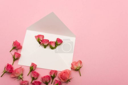 top view of white envelope with small tea roses isolated on pink