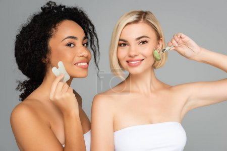 Photo for Multiethnic women with perfect skin massaging faces with gua sha and jade roller isolated on grey - Royalty Free Image