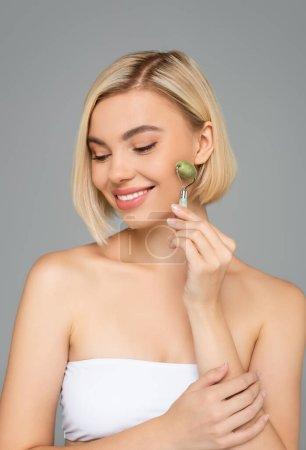 Lächelnde Frau in weißem Top mit Jade-Rolle isoliert auf grau