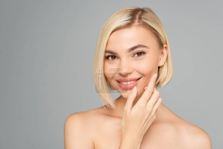 Smiling blonde woman applying cosmetic cream on cheek isolated on grey