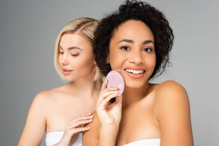 Photo for Smiling african american woman holding silicone brush near blonde woman on blurred background isolated on grey - Royalty Free Image