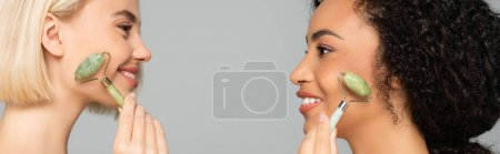 Photo for Side view of interracial women holding jade rollers near cheeks isolated on grey, banner - Royalty Free Image